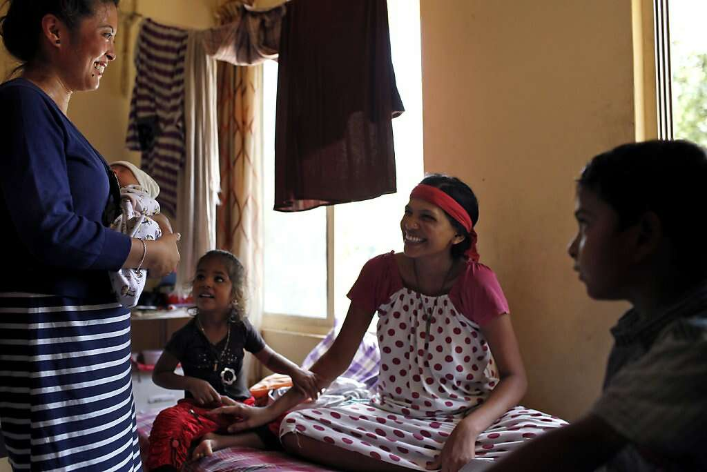 Four days after he was born, Jennifer Benito-Kowalski (left) introduces baby Kyle to surrogate Manisha Parmar and her children, Urvashi, 3, and Tanvay, 8, at the Akanksha Infertility Clinic in Anand, India, Monday, May 27, 2013. Photo: Nicole Fruge, The Chronicle