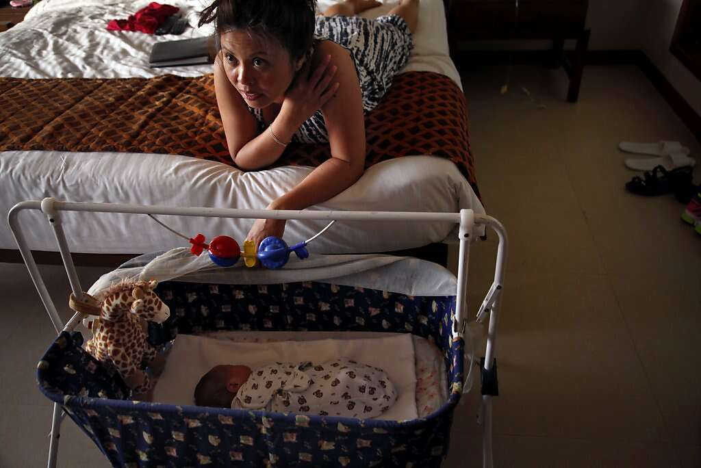 Jennifer Benito-Kowalski watches television as baby Kyle sleeps in their room at the Madhubhan Resort and Spa in Anand, India, Friday, May 24, 2013. Photo: Nicole Fruge, The Chronicle