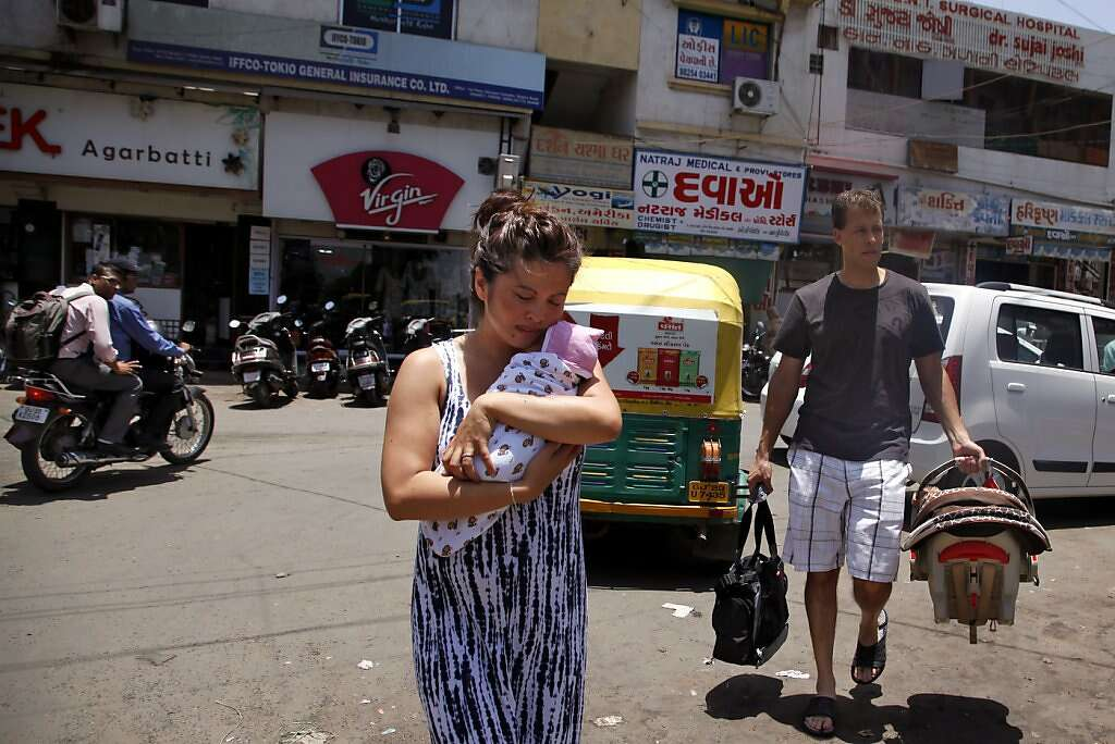 Jennifer Benito-Kowalski carries baby Kyle while husband Steve Kowalski follows with a car seat and diaper bag after Kyle was released from the Apara Nursing Home in Anand, India, Friday, May 24, 2013. Their hotel car never arrived, so the Kowalskis walked to the Akanksha Infertility Clinic to phone the hotel again. Photo: Nicole Fruge, The Chronicle