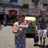 Jennifer Benito-Kowalski carries baby Kyle while husband Steve Kowalski follows with a car seat and diaper bag after Kyle was released from the Apara Nursing Home in Anand, India, Friday, May 24, 2013. Their hotel car never arrived, so the Kowalskis walked to the Akanksha Infertility Clinic to phone the hotel again.