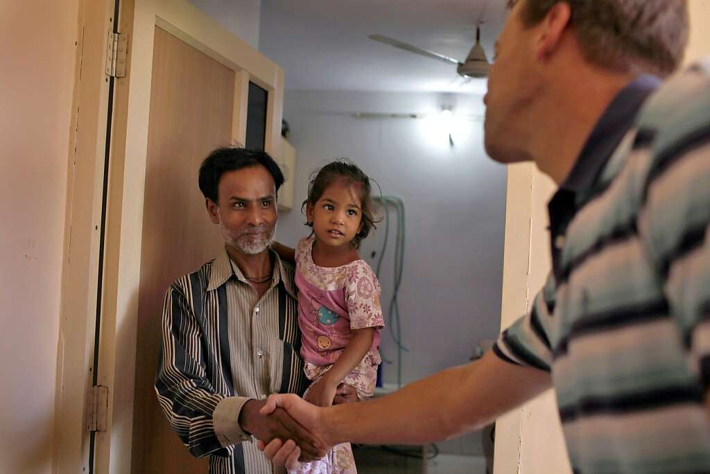 Steve Kowalski (right) thanks surrogate Manisha Parmar's husband, Raman, and daughter, Urvashi, 3, after she delivered a baby boy by cesarean section at the Akanksha Infertility Clinic in Anand, India, Thursday, May 23, 2013. Photo: Nicole Fruge, The Chronicle