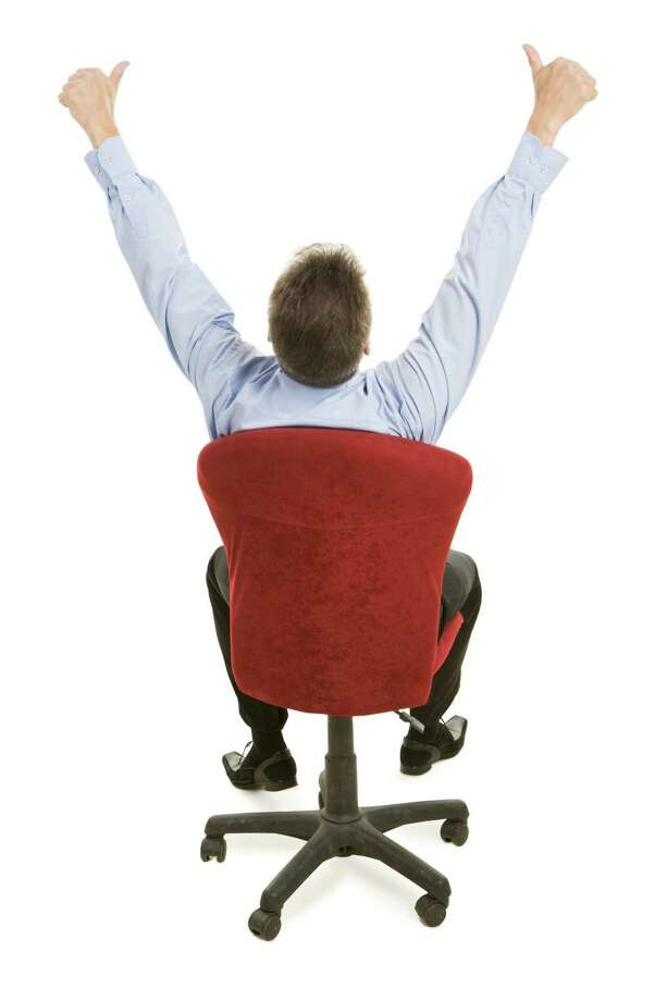 Rear view of boss sitting on the armchair and showing sign - okay 