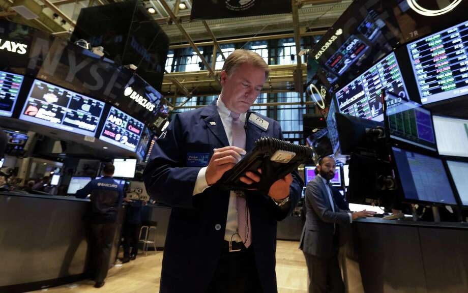 In this Sept. 18, 2013 file photo, Trader F. Hill Creekmore works on the floor of the New York Stock Exchange. Photo: Richard Drew, Associated Press / Associated Press