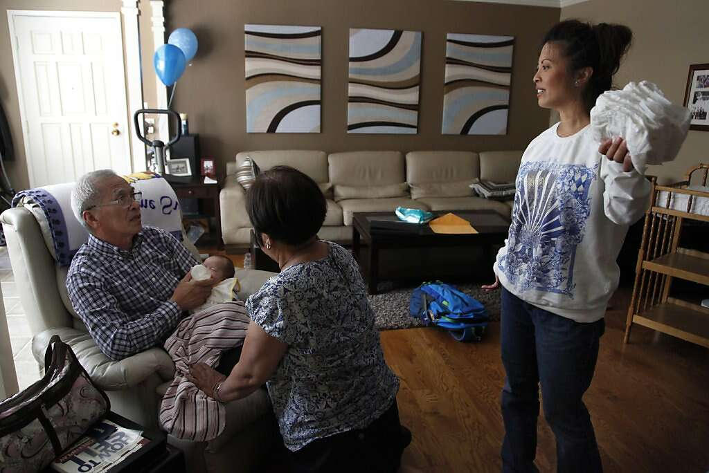 "Grandparents Domingo and  Clemencia ""Amy"" Benito feed baby Kyle as  Jennifer Benito-Kowalski looks on in her home in San Carlos, Calif., Wednesday, August 7, 2013. Photo: Nicole Fruge, The Chronicle"