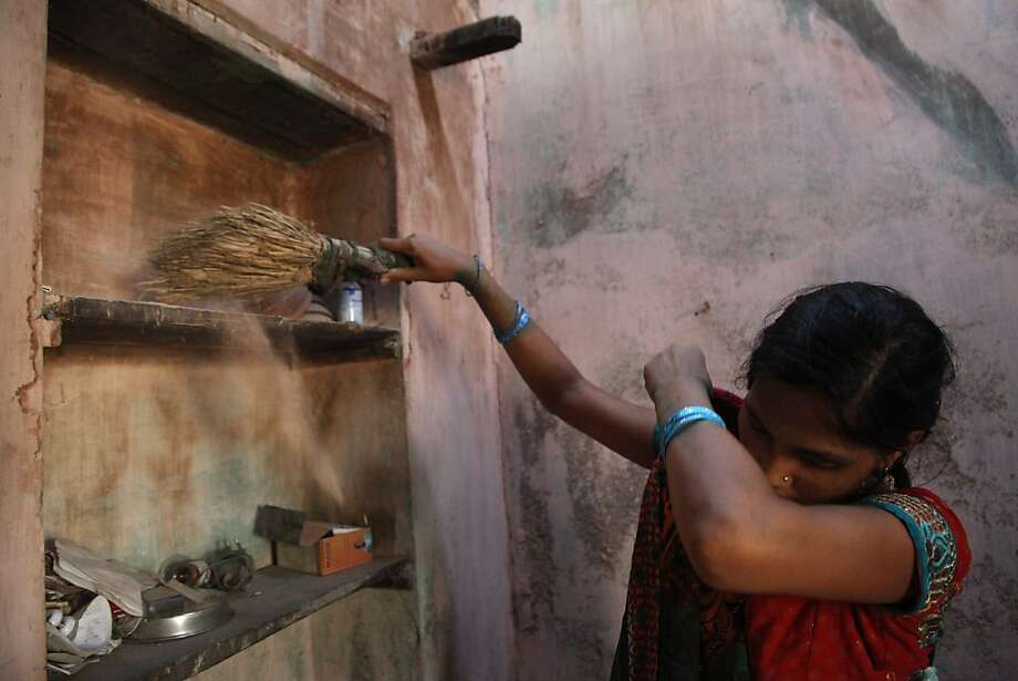 Manisha Parmar sweeps in her Khambhat, India, home, nine months after leaving and 11 days after giving birth for a Bay Area couple last spring. Photo: Nicole Fruge, The Chronicle