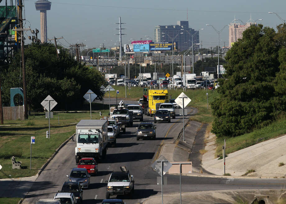Traffic backs up on Interstate 35 and the access road near the Binz-Engleman exit, where a woman apparently attempted suicide while driving, police said. After the shooting, the woman's blue Dodge Stratus ran into the interstate's median. Photo: Photos By John Davenport / San Antonio Express-News
