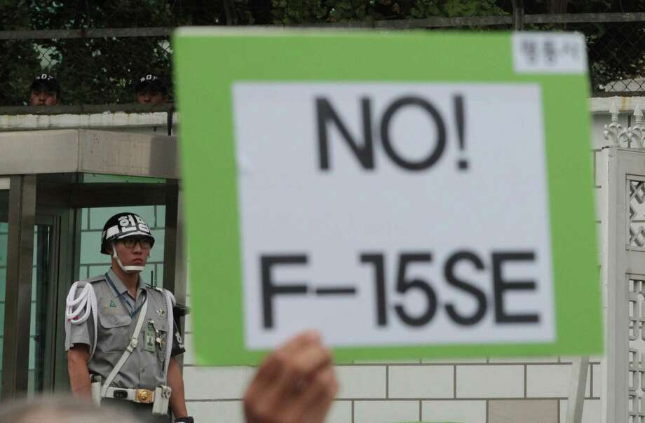 """A protester raises a card reading: """"No! F-15SE"""" during a rally against a meeting of senior military officers to choose South Korea's next-generation fighter jets as a military policeman stands guard in front of the Defense Ministry in Seoul, South Korea, Tuesday, Sept. 24, 2013. South Korea says it is delaying selection of a winning bidder to build 60 new fighter jets in a multibillion dollar weapons project. (AP Photo/Ahn Young-joon) ORG XMIT: SEL101 Photo: Ahn Young-joon / AP"""