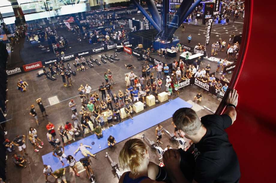 Annie Thorisdottir from Iceland (left) and Frederik Aegidius from Denmark watch as competitors compete in the CrossFit challenge at the UFC Fan Expo at the George R. Brown Convention Center, Friday, Oct. 7, 2011, in Houston. 