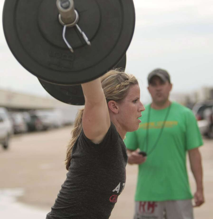 (l-r) Beth Spearman completes an overhead squat as her coach Jim Kelly keeps her time at Atomic CrossFit in Stafford,Texas, Wednesday, July 17, 2013. Spearman is part of a team of six members training for the Crossfit Games in Carson California that begin July 24. The team is comprised of 3 men and 3 women Beth Spearman, Janet Black, Jamie Carter, Daniel Ward ,Will Maloy, and Benjamin Bacon. ( Billy Smith II / Chronicle ) Photo: Billy Smith II, Chronicle