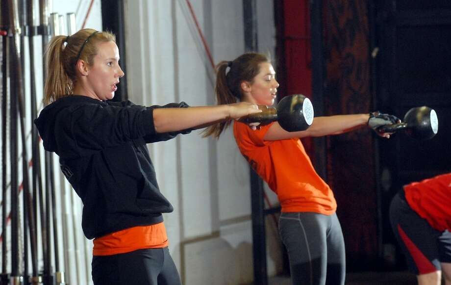 From left: Jennifer Sindelar and Tammy Adamo work out at the 6 a.m. class at Crossfit at their facility on Telephone Rd. Thursday Dec. 04, 2008. (Dave Rossman for the Chronicle) Photo: Dave Rossman, For The Chronicle