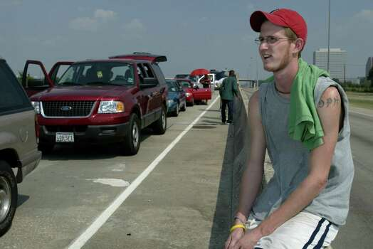 Davin Hogue, 21, of Beaumont, Texas, sits on the HOV lane divider while waiting for traffic to move along the Katy Freeway as Hurricane Rita approaches the Texas Gulf Coast Thursday, Sept. 22, 2005, in Houston. Photo: Kevin Fujii, Houston Chronicle / Houston Chronicle