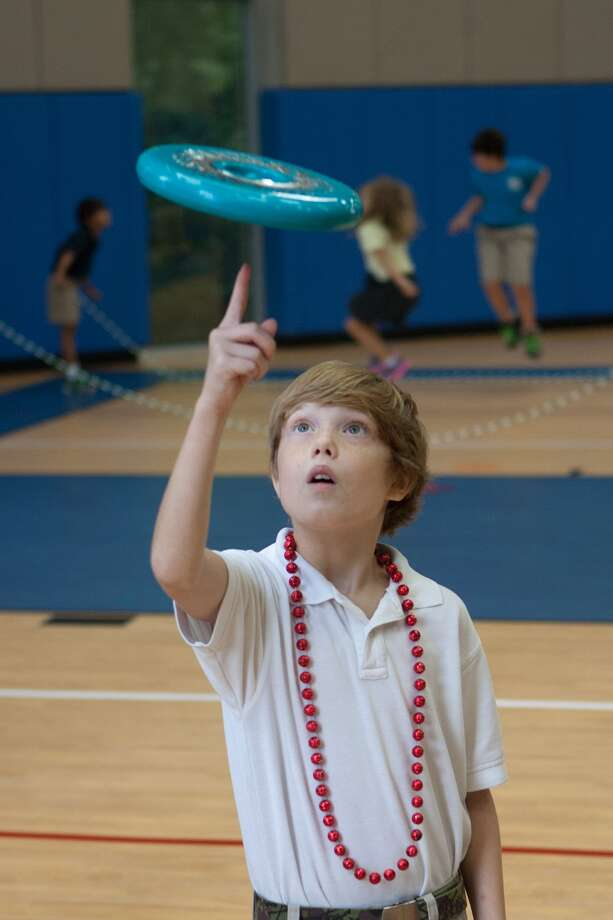 Simon Gross shows his stuff with a flying disk  in the new gymnasium at the Shlenker School. Photo: R. Clayton McKee, Freelance / ©2013 R. Clayton McKee