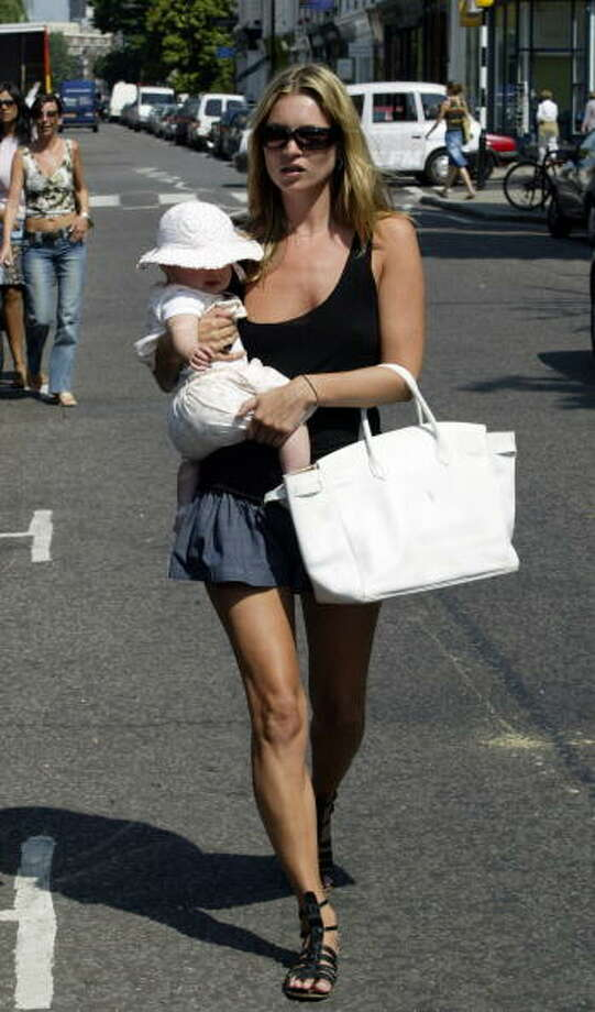 Kate Moss is pictured with daughter Lila Grace on June 24, 2003 in West London. The father of the child is Jefferson Hack, then a magazine editor and Moss' boyfriend. Photo: Aura, Getty Images / 2003 Getty Images
