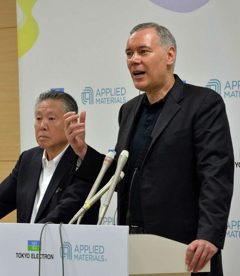 Japan's Tokyo Electron chairman Tetsuro Higashi (L) and US semiconductor giant Applied Materials CEO Gary Dickerson (R) announce their agreement to merge next year at a press conference at the Tokyo Electron headquarters in Tokyo on September 24, 2013. Applied Materials and Tokyo Electron, US and Japanese makers of tools to produce semiconductors and displays, said they will merge to increase efficiency and to better meet changing customer demands.    AFP PHOTO / Yoshikazu TSUNOYOSHIKAZU TSUNO/AFP/Getty Images Photo: YOSHIKAZU TSUNO / AFP