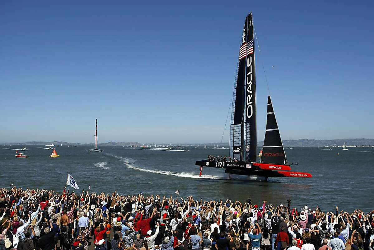 Oracle Team USA crosses the finish line ahead of Emirates Team New Zealand to win race 17 of the America's Cup Finals in San Francisco, CA Tuesday September 24, 2013.
