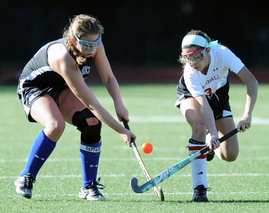 At left, Molly Riegel (# 24) of Darien goes for the ball against Sydney Cole (# 3) of Greenwich during the girls high school field hockey match between Greenwich High School and Darien High School at Cardinal Stadium, Greenwich, Tuesday, Sept. 24, 2013. Darien defeated Greenwich, 5-1. Photo: Bob Luckey / Greenwich Time