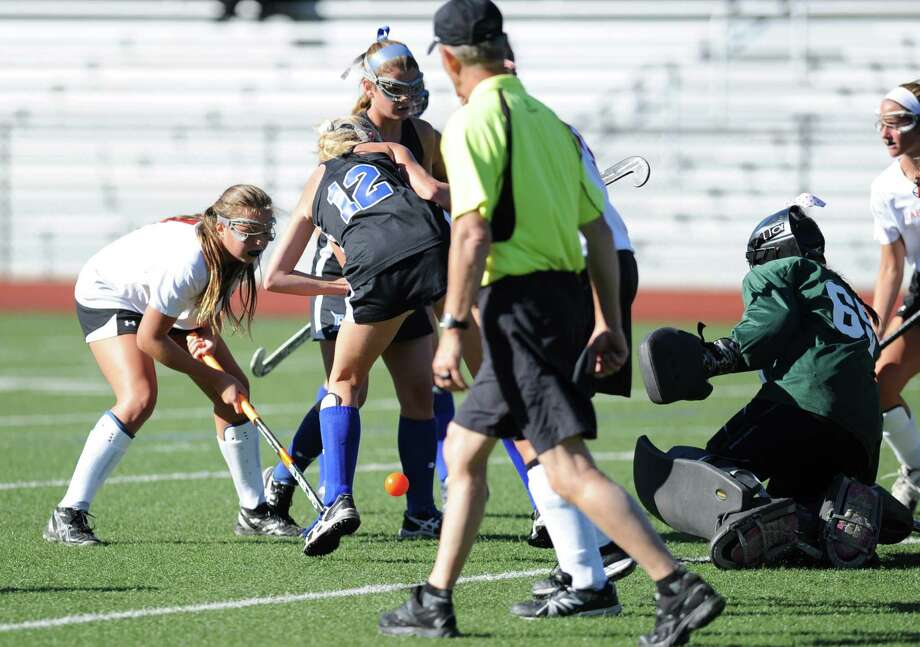 Greenwich goalie, Freddie Bancroft, right, searches for the ball through a small group of players including Darien's Claire Culliton (#12) during the girls high school field hockey match between Greenwich High School and Darien High School at Cardinal Stadium, Greenwich, Tuesday, Sept. 24, 2013. Darien defeated Greenwich, 5-1. Photo: Bob Luckey / Greenwich Time
