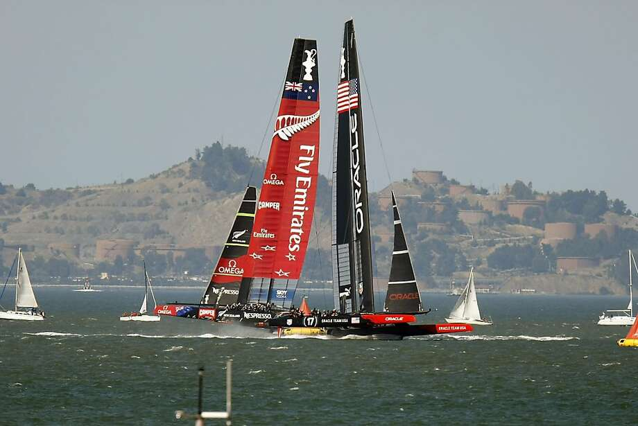 Emirates Team New Zealand and Oracle Team USA pass as they turn at the leeward mark during Race 18. Oracle took the lead for good on the upwind third leg, winning its second race of the day and seventh straight to tie the finals 8-8 with one race to go. Photo: Michael Short, The Chronicle