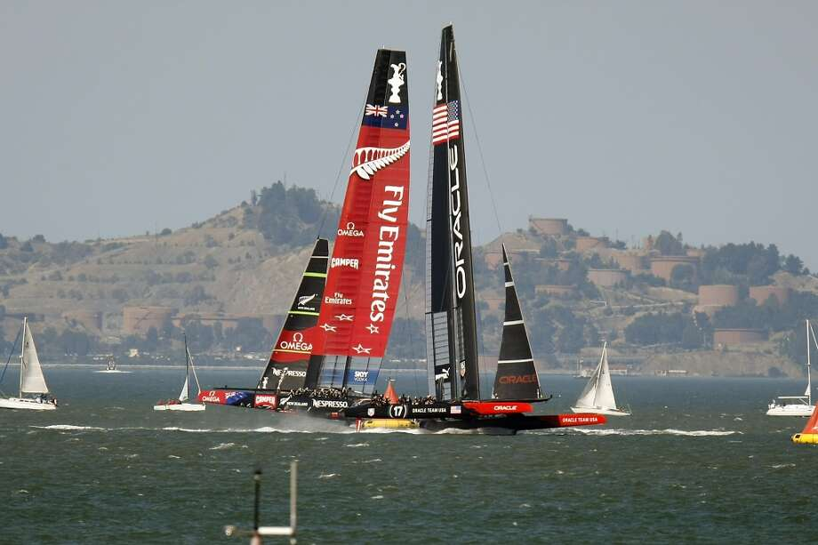 Emirates Team New Zealand, left, and Oracle Team USA pass each other as they make the turn at the leeward marks during race number 18 of the America's Cup Finals in San Francisco, CA Tuesday September 24, 2013.  Oracle would eventually catch and pass Emirates to win race 18 to tie the series and force a winner-take-all race scheduled for Wednesday. Photo: Michael Short, The Chronicle