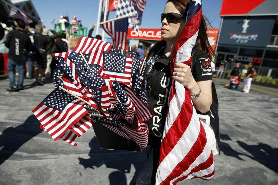 Oracle employee Brandi List carries a box of flags to give out to supporters before the start of race 17 of the America's Cup Finals in San Francisco, CA Tuesday September 24, 2013. Photo: Michael Short, The Chronicle