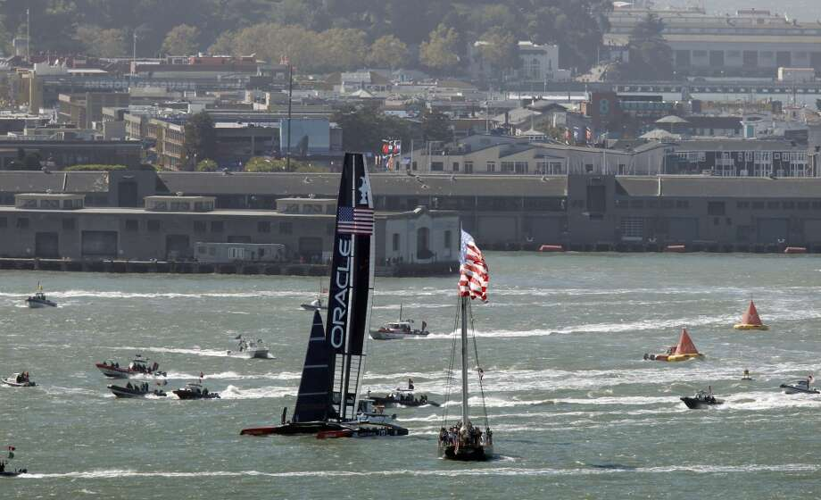Oracle Team USA glides past America's Cup Park after winning race 18 over Emirates Team New Zealand to tie the score at 8-8 as the America's Cup continues on San Francisco Bay, Calif., on Tuesday Sept. 24, 2013. Photo: Michael Macor, The Chronicle