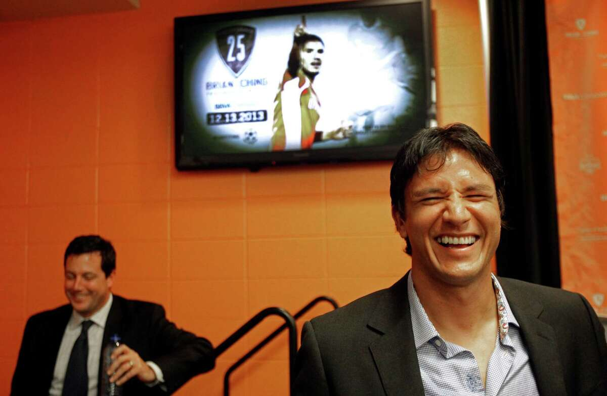Houston Dynamo president Chris Canetti is shown left as Houston Dynamo forward Brian Ching, right, shares a laugh with members of the media after a media conference about his retirement held at BBVA Compass Stadium Tuesday, Sept. 24, 2013, in Houston. The Houston Dynamo and Dynamo Charities will host a Brian Ching Testimonial Match on Dec. 13. The event will benefit, The House That Ching Built, which is Ching's partnership with Houston Habitat for Humanity.