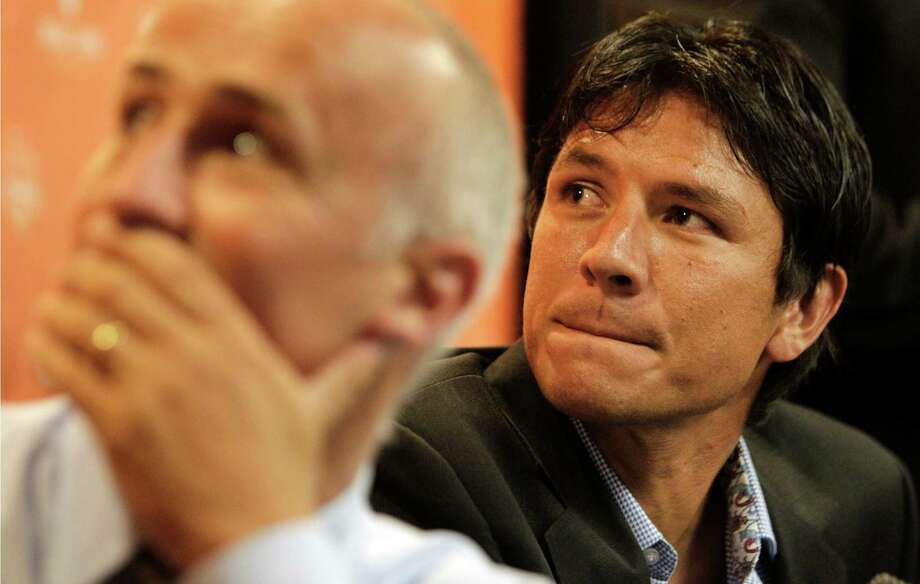 Houston Dynamo coach Dominic Kinnear, left, and player Brian Ching, right, watch a video tribute to Ching during a media conference  during a media conference about Ching's retirement at BBVA Compass Stadium Tuesday, Sept. 24, 2013, in Houston. The Houston Dynamo and Dynamo Charities will host a Brian Ching Testimonial Match on Dec. 13. The event will benefit, The House That Ching Built, which is Ching's  partnership with Houston Habitat for Humanity. Photo: Melissa Phillip, Houston Chronicle / © 2013  Houston Chronicle