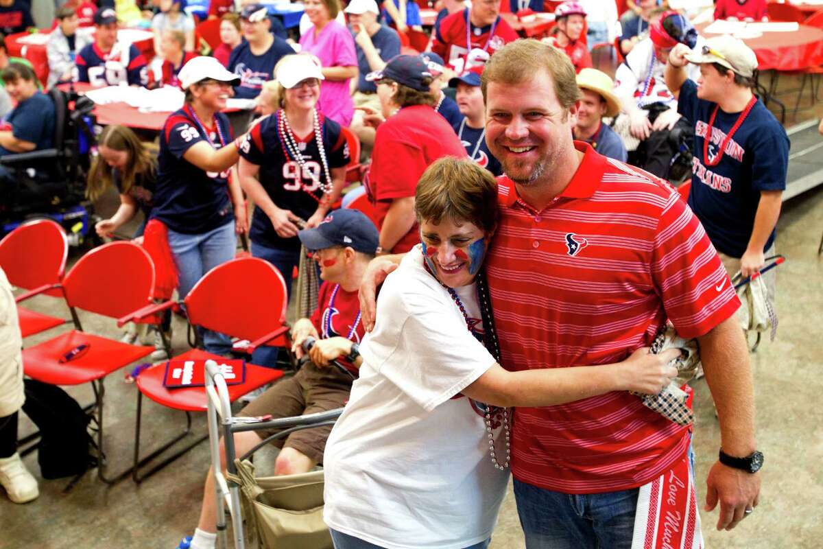 Houston Texans punter Shane Lechler embraces Brookwood Community citizen Michelle, during a visit by Lechler, kicker Randy Bullock and long snapper Jon Weeks Tuesday, Sept. 24, 2013, in Brookshire.