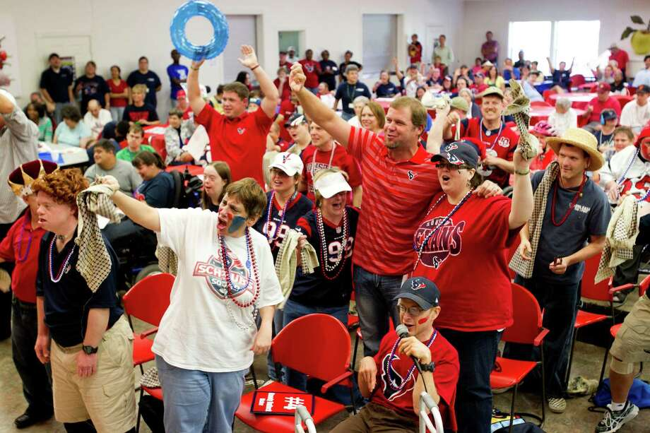 Houston Texans punter Shane Lechler, center, cheers with citizens of the Brookwood Community during a pep rally with fellow Texans, kicker Randy Bullock , and long snapper Jon Weeks, far left, Tuesday, Sept. 24, 2013, in Brookshire. Photo: Brett Coomer, Houston Chronicle / © 2013 Houston Chronicle