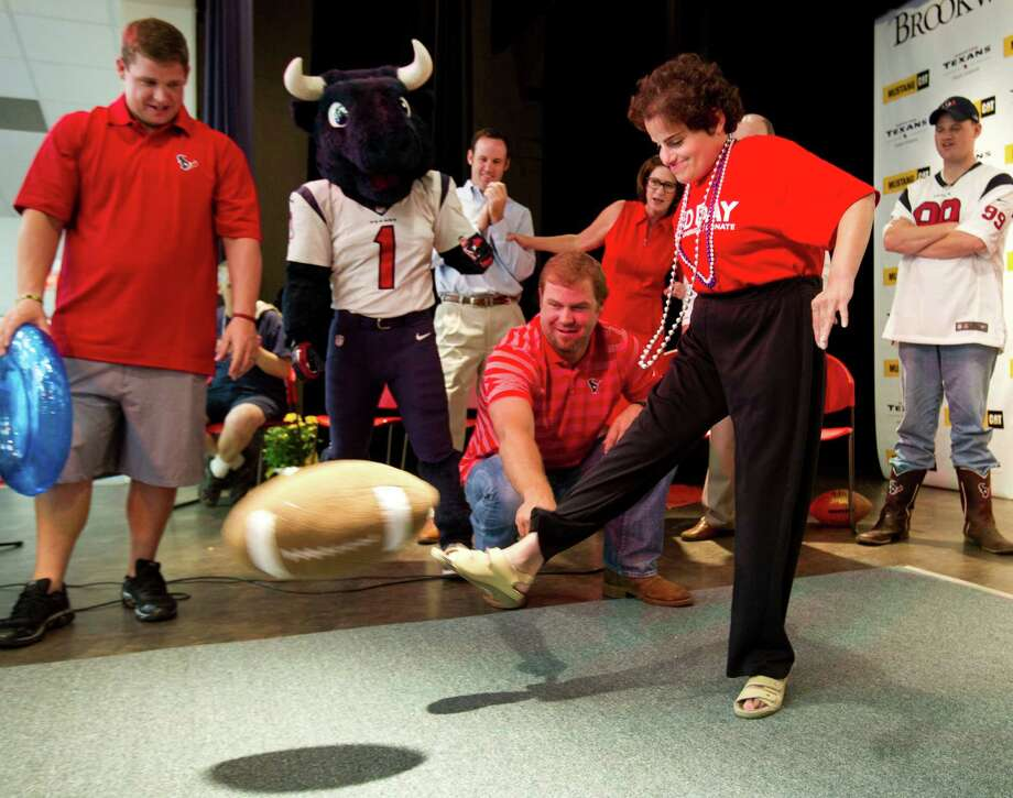 Houston Texans punter Shane Lechler holds a plush football for Linley, a Brookwood Community citizen, to kick during a pep rally at the facility Tuesday, Sept. 24, 2013, in Brookshire. Photo: Brett Coomer, Houston Chronicle / © 2013 Houston Chronicle