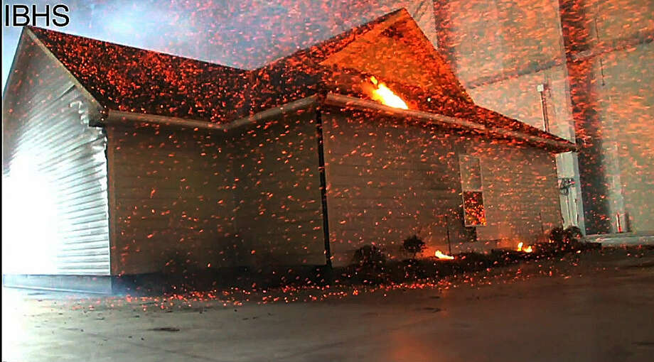 A frame grab from video shows embers being shot at a test house by the National Institute of Standards and Technology, whose researchers are analyzing behavior of wind-driven embers as fuel for wildfires. Photo: Associated Press