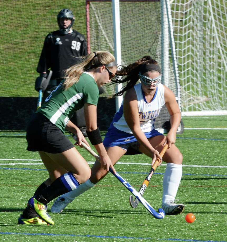 Newtown's Emily Davis and New Milford's Corinne Heymach fight for possession during a field hockey game at Newtown on Tuesday Sept. 24, 2013 Photo: Lisa Weir / The News-Times Freelance