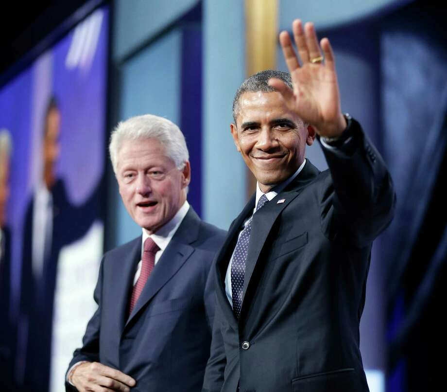 President Barack Obama acknowledges members of the audience after Tuesday's appearance with former President Bill Clinton, left, in New York. Photo: Pablo Martinez Monsivais, STF / AP