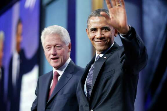 President Barack Obama acknowledges members of the audience after Tuesday's appearance with former President Bill Clinton, left, in New York.