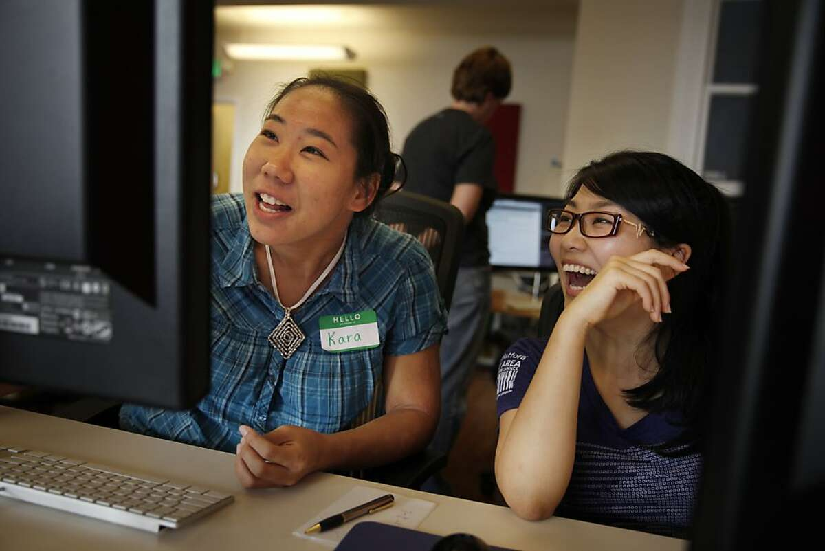 Hackbright Academy students Kara Louie (l to r) and Jennie Ohyoung share a laugh as they work on pair programming on the first day of class of the Hackbright Academy Programming Fellowship at Hackbright Academy on Monday, September 23, 2013 in San Francisco, Calif.