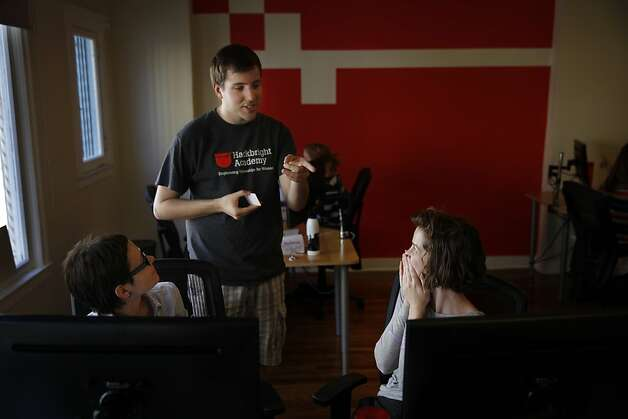 Hackbright Academy students Gosia Migdal (left) and Katie Lefevre get help from instructor Nick Audo as they work on their first day of class. Photo: Lea Suzuki, The Chronicle