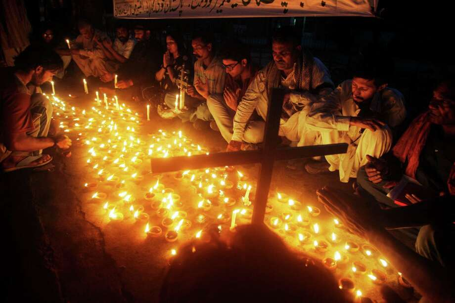 Pakistanis light candles to express their solidarity with the victims of Sunday's Peshawar suicide attack on a church in Lahore, Pakistan, Tuesday, Sept. 24, 2013. Pakistani Christians denounced the deadliest attack ever in this country against members of their faith when a pair of suicide bombers blew themselves up amid hundreds of worshippers outside a historic church in northwestern Pakistan on Sunday, Sept. 22, 2013.  (AP Photo/K.M. Chaudary) Photo: K.M. Chaudary, STR / AP
