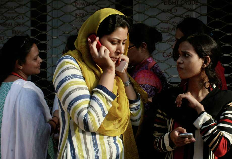A Pakistani woman speaks on her mobile phone after rushing out of her apartment following a major earthquake that struck Baluchistan province in southwest Pakistan, 693 Kilometers (430 miles) from Karachi, Pakistan, Tuesday, Sept. 24, 2013. A deadly earthquake struck Tuesday in southwestern Pakistan sending poeople fleeing into the streets and praying for their lives as buildings swayed, officials said. Photo: Shakil Adil