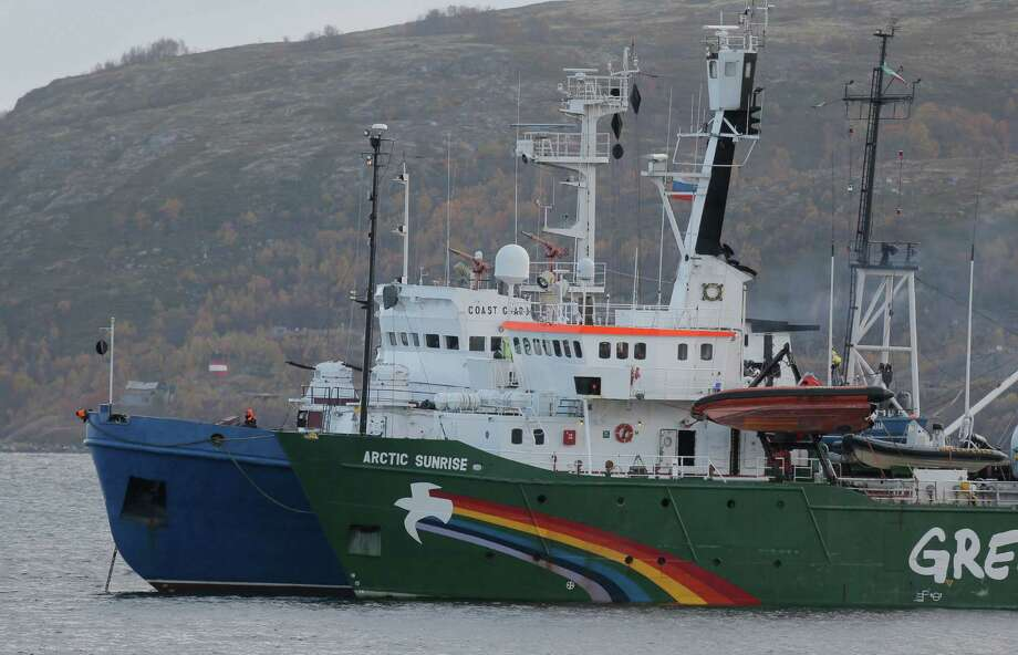 A Greenpeace ship is escorted by a Russian coast guard vessel to a military base at dawn Tuesday after activists tried to board an Arctic drilling platform. Photo: Efrem Lukatsky, STF / AP