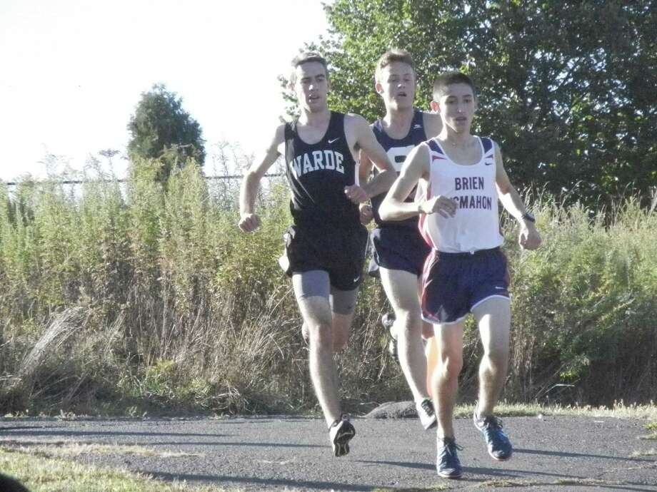 Aidan Fiol, left, of Warde, with Oliver Hickson, center, of Staples, and Eric van der Els, of McMahon, in the middle of the boys cross country race at Staples on Tuesday, Sept. 24 in Westport. Staples won all four boys races and all four girls races. Photo: Reid L. Walmark / Fairfield Citizen