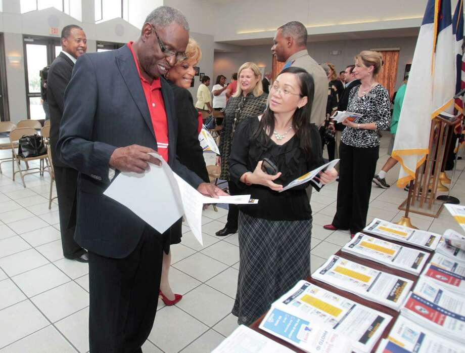 Holman Street Baptist Church deacon Roy Phillips gets information from  Voter Outreach Coordinator Du-Ha Kim Nguyen at the Harris County Clerk's Office. Photo: Billy Smith II, Staff / © 2013 Houston Chronicle
