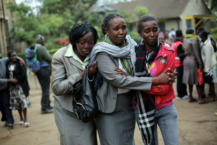 Relatives of Johnny Mutinda Musango, 48, weep after identifying his body at the city morgue  in Nairobi, Kenya, Tuesday Sept. 24 2013. Musango was one of the victims of the Westgate Mall hostage siege. Kenyan security forces were still combing the Mall on the fourth day of the siege by al-Qaida-linked terrorists. (AP Photo/ Jerome Delay) ORG XMIT: XJD105 Photo: Jerome Delay / AP