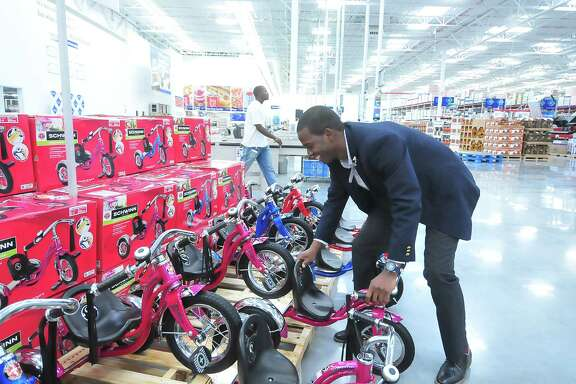 Store manager Robert Williams helps stack tricycles in preparation for the opening of the Sam's Club at 13331 Westheimer.
