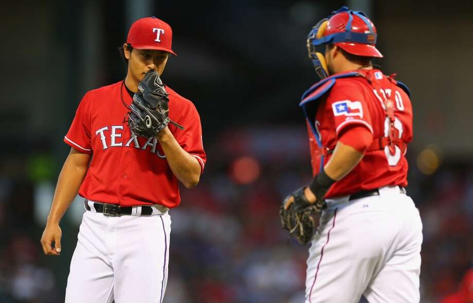 Rangers pitcher Yu Darvish shares a word with catcher Geovany Soto while playing the Astros. Photo: Ronald Martinez, Getty Images