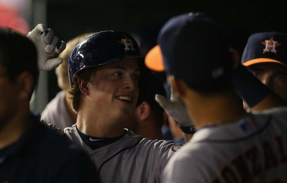 Astros third baseman Matt Dominguez is congratulated by teammates in the dugout after hitting a home run against the Rangers. Photo: Ronald Martinez, Getty Images