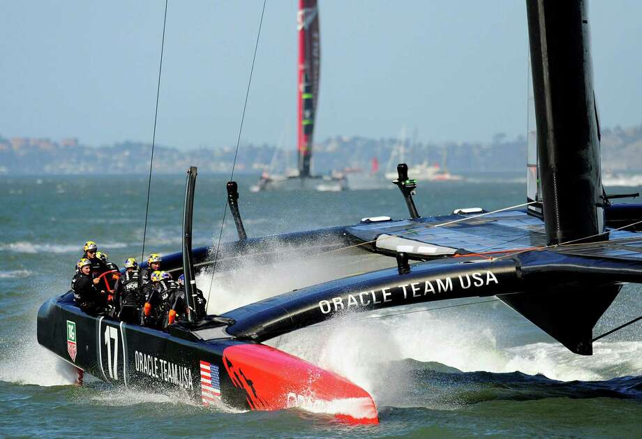 Oracle Team USA makes a splashy crossing of the final line while winning. Photo: JOSH EDELSON, Stringer / joshedelson@gmail.com