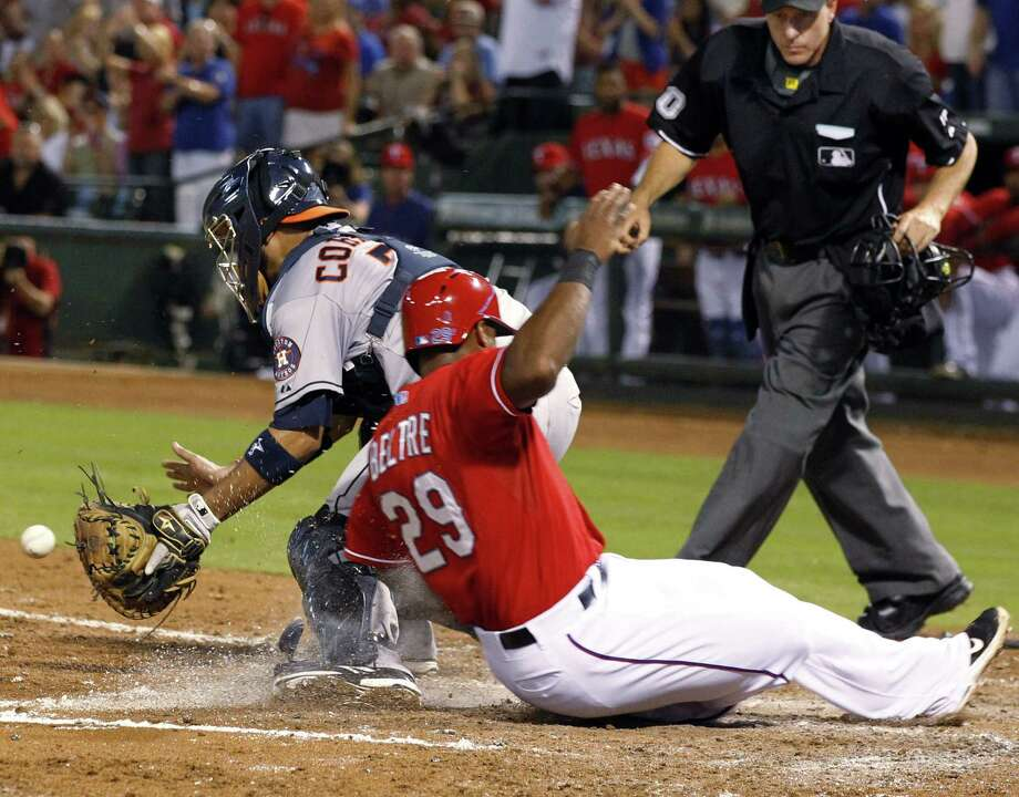 The Rangers' Adrian Beltre slides into home past Astros catcher Carlos Corporan during the fourth inning. He scored on Geovany Soto's single, which tied the game at 1-1. Photo: John F. Rhodes / Associated Press