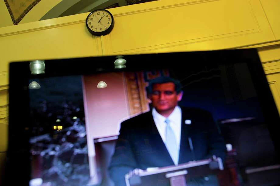 Sen. Ted Cruz, R-Texas, is seen on a television screen in the Senate Press Gallery during the tenth hour of his speech on the Senate floor on Wednesday, Sept. 25, 2013 in Washington. Cruz began a lengthy speech urging his colleagues to oppose moving ahead on a bill he supports. The measure would prevent a government shutdown and defund Obamacare. Photo:  Evan Vucci