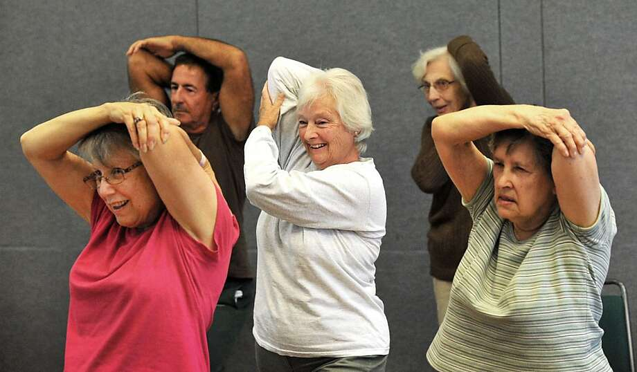 The arm bone's connected to the... Dolly Jennings, 73, is at the center of a group strech during Strength Training at the Danbury Senior Center in Danbury, Conn. Photo: Michael Duffy