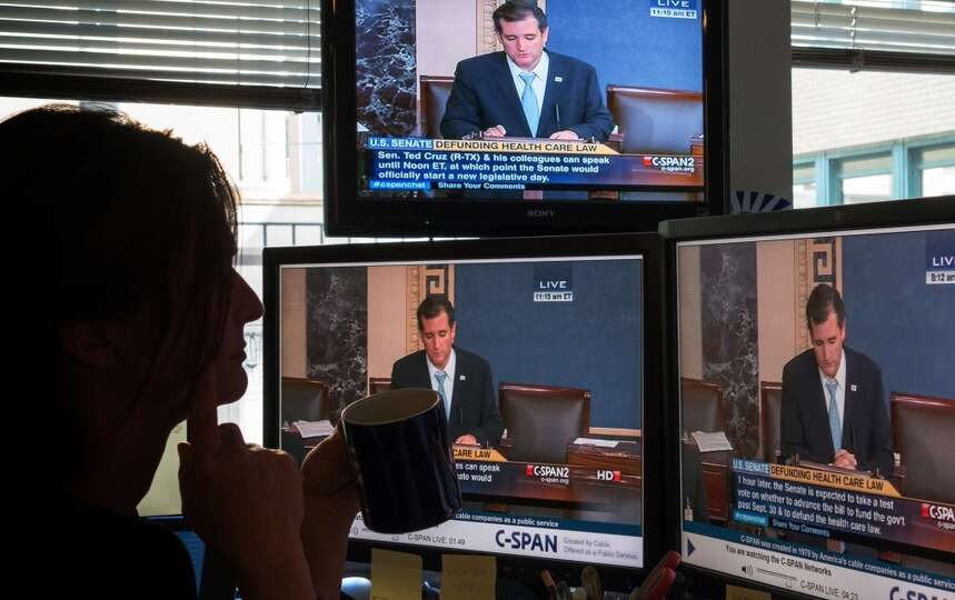 A journalist watches C-SPAN  TV on computer screens showing US Senator Ted Cruz (R-TX) on September
